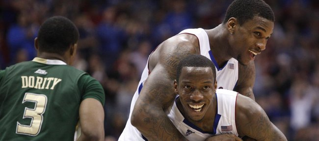 Kansas forward Thomas Robinson, top, hugs teammate Tyshawn Taylor after Taylor's feed to Robinson for a dunk against South Florida during the second half on Saturday, Dec. 3, 2011 at Allen Fieldhouse.