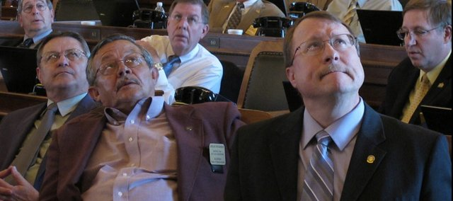 Kansas House Pensions Committee Chairman Mitch Holmes, far right, listens during a pensions legislation debate at the Statehouse Tuesday, May 10, 2011. Behind him is Rep. Leslie Osterman, a Wichita Republican. 