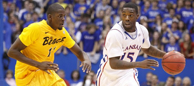 Kansas guard Elijah Johnson looks to push the ball up the court as he is defended by Long Beach State forward James Ennis during the first half on Tuesday, Dec. 6, 2011 at Allen Fieldhouse.