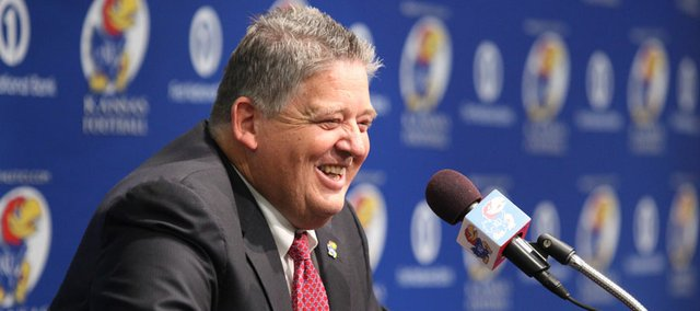 Charlie Weis laughs at the podium as he addresses media members during a news conference in which Weis was announced as the new football coach for KU on Friday, Dec. 9, 2011 at the Anderson Family Football Complex.