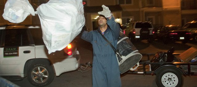 Armond Enclard tosses a bag of trash into a bin at the the Connection, 31st and Ousdahl, on one of his nightly recycling runs. Enclard operates a recycling business where he goes door to door in complexes like the Connection to pick up people's recyclables.