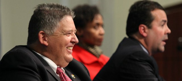 Charlie Weis laughs as he sits at a table with Kansas University athletic director Sheahon Zenger and Chancellor Bernadette Gray-Little during a news conference in which Weis was announced as the new head football coach Friday, Dec. 9, 2011 at the Anderson Family Football Complex.