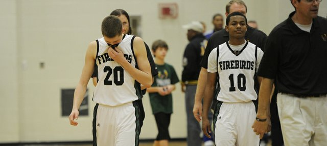 Free State senior guards Tyler Self (20) and Shawn Knighton walk off the court after Firebirds' 46-44 loss to Lansing on Saturday at FSHS.