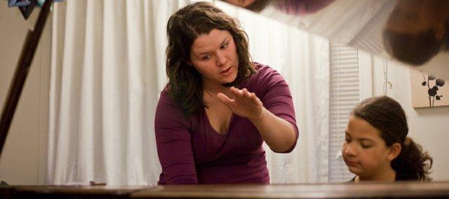 Lawrence piano teacher Jamie Bone instructs student Ashlyn Norwood, 9, at Bone's home.