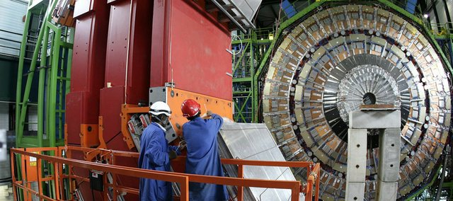 In this 2007 file photo, two engineers work to assemble one of the layers of the world's largest superconducting solenoid magnet (CMS, Compact Muon Solenoid) at the European Organization for Nuclear Research (CERN)'s Large Hadron Collider (LHC) particle accelerator, in Geneva, Switzerland. More than 20 researchers from Kansas University have contributed to work in the Large Hadron Collider.