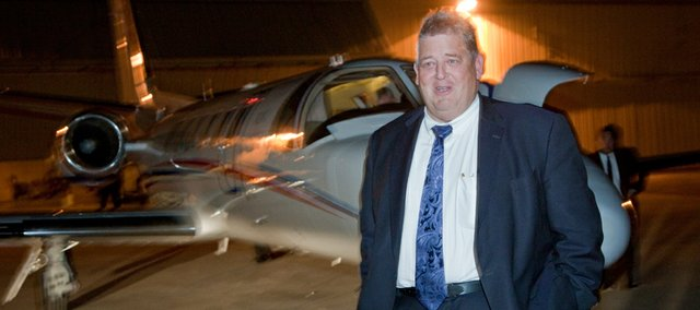 The hiring of Charlie Weis, as KU's new football coach provided staff photographers Nick Krug and myself three different photo events to cover on his arrival to Lawrence. The trickiest for me was a night time coverage of Weis's arrival at the Lawrence airport. Getting correct flash exposures and photographing through glass were two problems I dealt with to capture the new coach.