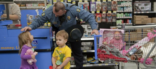 Kansas Highway Patrol Master Trooper Dennis Shoemaker completes a shopping trip with Aerianna Pool, 3, and Jacob Clark, 2 1/2 on Friday, Dec. 16, 2011 at Wal-Mart, 550 Congressional Drive. Area law enforcement officers, including the Douglas County Sheriff's Office, Kansas Highway Patrol, Lawrence Police and KU Office of Public Safety, participated in a breakfast at McDonald's and a Christmas shopping trip with 40 children who attend Ballard Community Services' early education programs. The shopping was funded by Hallmark Cards.