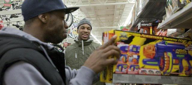 Elijah Johnson, left, and Thomas Robinson shop for gifts with other members of the KU men's basketball team Thursday night, Dec. 15, 2011 at Wal-Mart on south Iowa. The team shopped to fill Christmas gift lists for 15 families.