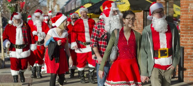 Stephanie Roberts, front left, and Shannon Gray, right, lead participants in the 2nd annual SantaCon on Saturday, Dec. 17, 2011. SantaCon combined elements of flash mob and a pub crawl with Christmas carols and random acts of kindness. This year it included a food drive to benefit Just Food, the primary food bank for Douglas County.