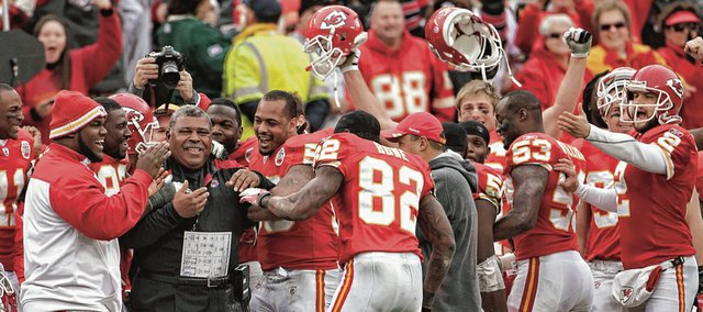 Interim coach Romeo Crennel (in black at left) celebrates with the Chiefs late in their 19-14 victory over Green Bay. The outcome Sunday in Kansas City, Mo., spoiled the Packers' perfect season and gave the struggling Chiefs a lift.