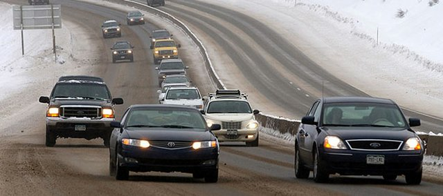 Cars travel over Vail Pass during a lingering winter storm in the Colorado mountains in this 2005 photo near Vail, Colo. More than 91.9 million Americans plan to travel throughout the 11 days that encompass the Christmas and New Year's holidays, according to AAA. That's a 1.4 percent increase from last year.