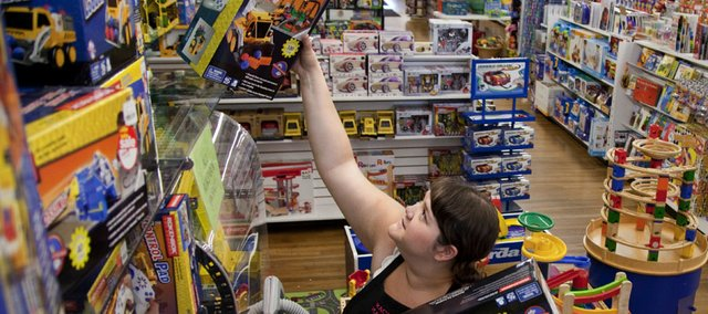 Store manager Rachel Ybarra pulls sale items from the shelves of The Toy Store, 936 Massachusetts, as she and other staff members work in this 2010 file photo. Many stores in Lawrence and across the country that are reporting stronger sales than last holiday season.