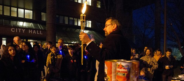 Lawrence mayor Aaron Cromwell holds a candle as a menorah made from cans of food is dedicated outside of City Hall Wednesday, Dec. 21, 2011 in downtown Lawrence. Approximately 560 cans of food were collected which will be distributed to pantries throughout Lawrence.