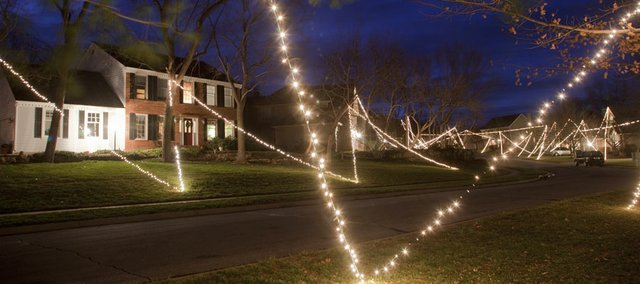 A zigzagging string of Christmas lights connects a neighborhood of homes and trees just north of Quail Run School on Woodridge Drive. Chad Dodd and Chris Eagle are the neighbors who provide and install the lights each year.