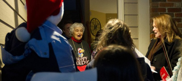 Becky Wisdom, center, sings along with Christmas carolers on the porch of her southwest Lawrence home Friday, Dec. 23, 2011.