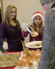Volunteers Erika Harbrecht, Eudora, left, and her daughter Jordan Lounce, 9, serve up a Christmas meal Sunday during the annual Lawrence Free Community Christmas Day Dinner at First United Methodist Church.