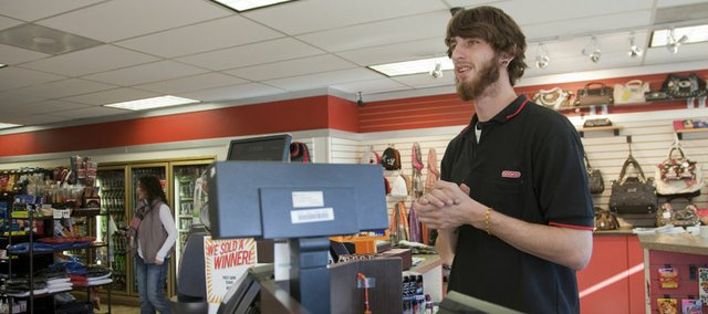 "Tory Runnells, Lawrence, works a Christmas day shift at the FastLane Conoco, 1414 Sixth St.., on Sunday. Runnells, who opened the shop, said it was a little slow early but picked up at mid-day. ""Batteries have been popular,"" Runnells said."