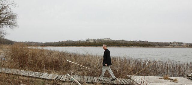 Dick Stuntz, president of Alvamar Inc., walks along a dock that should be floating in Lake Alvamar, formerly called Yankee Tank Lake, on March 18, 2009. A new top, a wider spillway and broader base will be added to the Lake Alvamar dam during the coming year, fortifying flood protection for a major road, a state highway and recreational complex downstream.