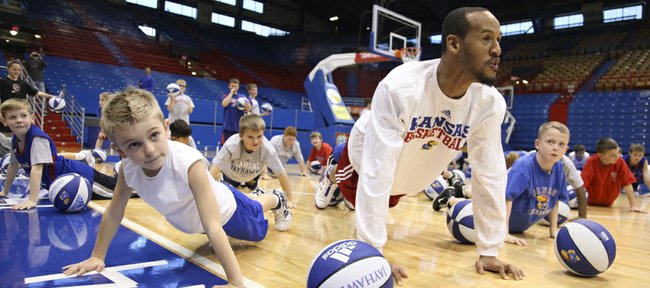 """Kansas guard Travis Releford gets down for """"hound dog pushups"""" next to 8-year-old Tyler Peterson, left, Topeka, on Tuesday, Dec. 27, 2011, during the Holiday Hoops Clinic at Allen Fieldhouse. The pushups, which were ordered by director of basketball operations, Barry Hinson, consisted of lifting one's head up and howling like a dog."""