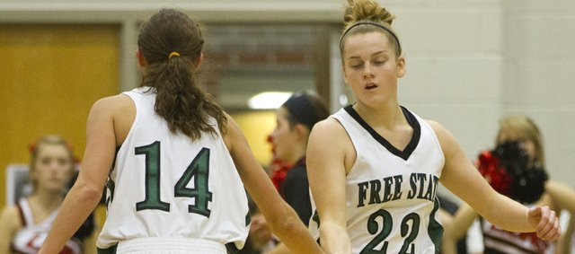 Free State's Lynn Robinson (14) congratulates Scout Wiebe (22) following a basket against Lawrence High on Friday, Dec. 16, 2011 at FSHS.