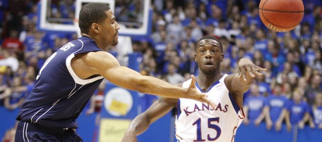 Kansas guard Elijah Johnson pass around Howard guard Glen Andrews during the first half on Thursday, Dec. 29, 2011 at Allen Fieldhouse.