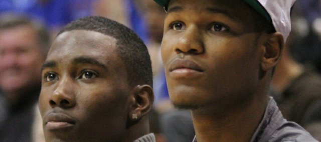 Kansas freshmen Jamari Traylor, left, and Ben McLemore  watch the Late Night in the Phog festivities from the bench on Friday, Oct. 14, 2011 at Allen Fieldhouse.