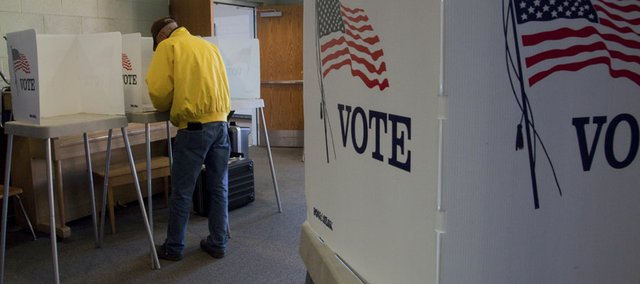 A man votes at New York Elementary School in this 2011 file photo. An election law written by Secretary of State Kris Kobach, which requires photo ID to vote, is raising concerns about what that means for absentee voting.