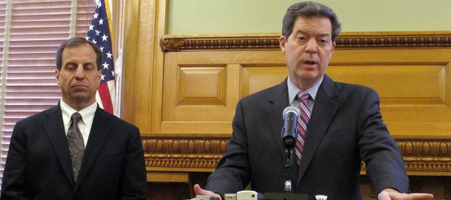 Kansas Gov. Sam Brownback, right, answers questions from reporters about Boeing's decision to close its Wichita defense plant by the end of 2013, as state Commerce Secretary Pat George, left, watches, during a news conference, Wednesday, Jan. 4, 2012, at the Statehouse in Topeka, Kan.