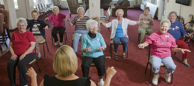 "A group of women laugh about an exercise that has them mimic playing a piano during a morning workout in October at Meadowlark Estates, 4430 Bauer Farm Drive, led by activity director Andrea Wyatt. ""Are we playing Mozart?"" inquired one woman. The Douglas County Retiree Attraction Task Force is on a mission to make Lawrence a retirement destination."