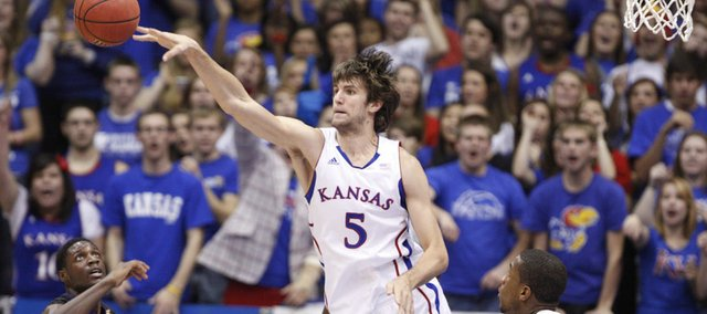 Kansas center Jeff Withey knocks a loose ball out to the wing over Kansas State forward Jamar Samuels during the first half on Wednesday, Jan. 4, 2012 at Allen Fieldhouse. At right is Kansas forward Thomas Robinson.