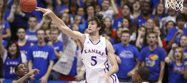 Kansas center Jeff Withey knocks a loose ball out to the wing over Kansas