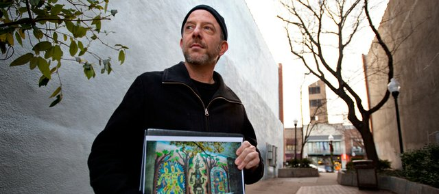 "Lawrence muralist Dave Loewenstein is pictured with a print of his 1993 mural ""Guardians of the Arts,"" which formerly existed on the north wall of the Signs of Life building at 722 Mass. The mural was recently painted over as repairs were needed on the building's north facade. Loewenstein is working to organize efforts to repaint the mural, which he says began his career as a community muralist."
