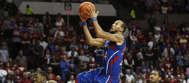 Kansas guard Travis Releford glides for a bucket between Oklahoma defenders Sam Grooms, left, and Steven Pledger during the second half Saturday, Jan. 7, 2012, at Lloyd Noble Center.