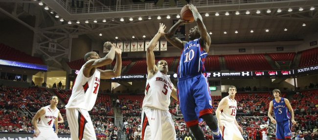 Kansas guard Tyshawn Taylor pulls up for a shot over Texas Tech defenders Javarez Willis (5) and Jaye Crockett during the first half Wednesday, Jan. 11, 2012, at United Spirit Arena.