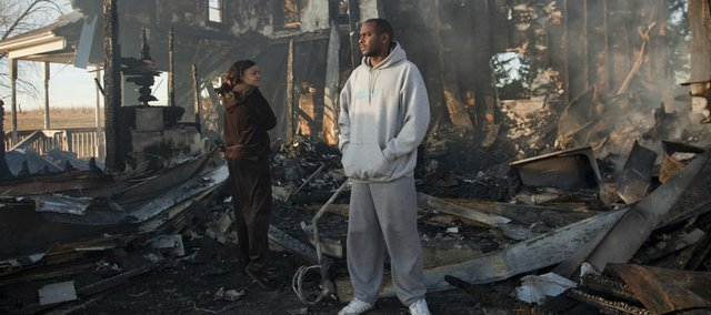 Roger and Camay Guilory stand outside their home at 1772 E. 200 Rd., which was destroyed in a fire early Friday morning, Dec. 29, 2011.  The parents and their nine children, ages 13-months to 19-years-old, escaped out a second-floor window.