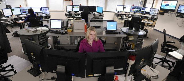 Lori Alexander works at her dispatcher station in a secure area of the Judicial & Law Enforcement Center, 111 E. 11th St., in this 2009 file photo. Douglas County Administrator Craig Weinaug said Friday he's recommending the city of Lawrence and Douglas County come up with $7 million in the near future to help the center that handles 911 calls and other emergency communications meet new federal technology standards.