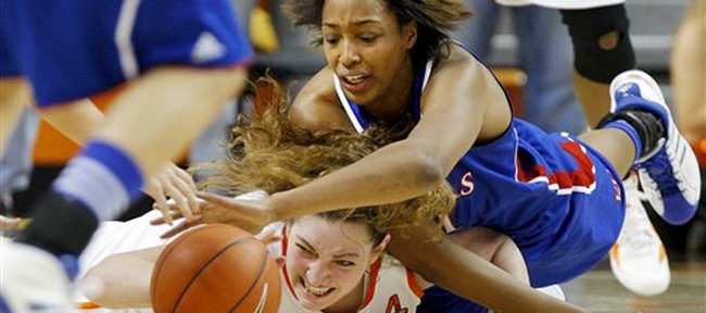 Oklahoma State's Lindsey Keller (25) and Kansas' Carolyn Davis (21) dive for the ball during Wednesday's game in Stillwater, Okla.. KU won, 65-60.
