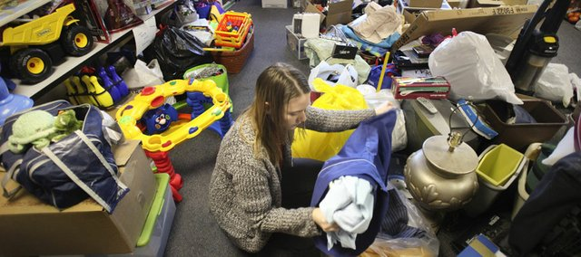 AmeriCorps volunteer Rene Romig sorts through piles of donations to be given to the family of Roger and Camay Guilory, on Wednesday, Jan. 18, 2012 at the United Way building, 2518 Ridge Court. The Guilory's home was destroyed in a Dec. 29 fire. Although the eleven-member-family is still in transition, local outreach organizations are organizing donations large and small for when they are settled.