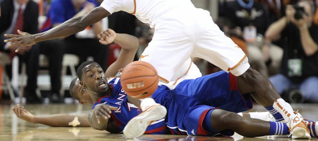 Kansas guard Elijah Johnson tosses a pass from the floor underneath Texas guard Myck Kabongo after a steal during the first half on Saturday, Jan. 21, 2012 at the Frank Erwin Center.