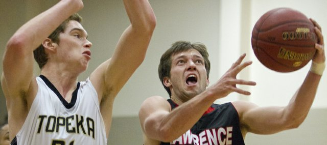 Lawrence High senior Troy Willoughby (12) gets past Evan Robinson (21) as he drives to the basket during Lawrence High's game against Topeka High in the Topeka Invitational Friday, Jan. 20, 2012 in Topeka.