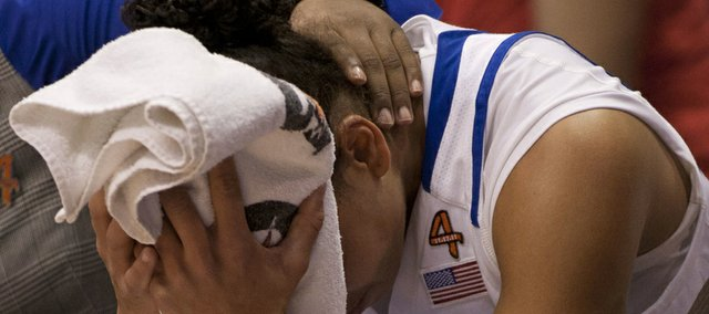 Kansas guard Angel Goodrich is consoled by coaches on the bench after fouling out during Kansas' game against Texas A&M Saturday, Jan. 21, 2012 at Allen Fieldhouse. The Jayhawks lost the game, 76-65.