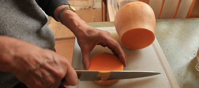 Natalya Lowther cuts up a butternut squash for making soup. Using cheap, seasonal ingredients, Lowther stretches her food dollar and maintains a healthy diet.