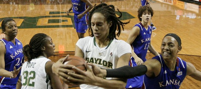 Baylor center Brittney Griner, center, grabs a rebound against Kansas' Aishah Sutherland (11) in the first half of Saturday's game in Waco, Texas. Griner had 28 points, seven rebounds and five blocks in the 74-46 Baylor win.