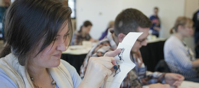 Erin Billing, of Topeka, works to run a needle through some sheets of paper while making a book during a bookbinding workshop Saturday at KU's Watson Library. Participants learned four structures of creating bound books without glue, including accordion and stitched books.