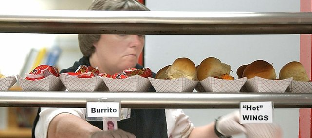 In this 2007 file photo, Nikki White works during a lunch period at Central Junior High School. Lawrence has already begun adapting to a change in federal food standards, which would replace hot dogs and bread with whole wheat spaghetti.