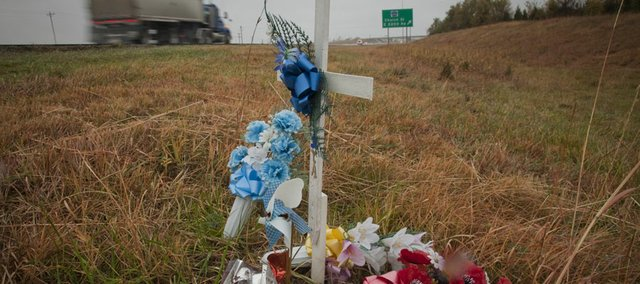 A wreath stands where 5-year-old Cainan Shutt of Eudora died in April in an accident on Kansas Highway 10 east of Lawrence. A white cross for Ryan Pittman, 24, also killed in that crash, sits next to the highway. Carie Lawrence, the grandmother of 5-year-old Cainan Shutt, urged legislators on Wednesday to approve a bill that would double fines on the highway.