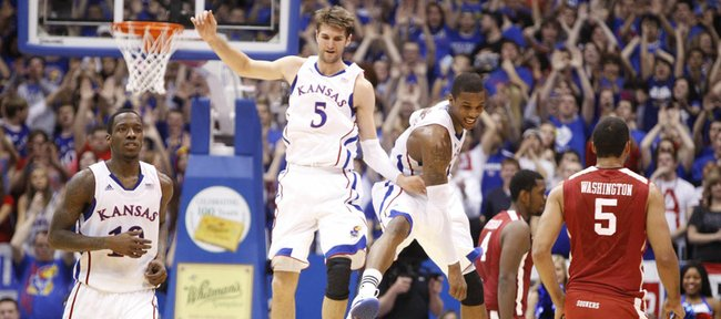 Kansas big men Jeff Withey (5) and Thomas Robinson get airborne as they celebrate a Jayhawk run against Oklahoma during the second half on Wednesday, February 1, 2012 at Allen Fieldhouse. At left is KU guard Tyshawn Taylor.