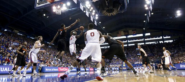 Kansas guard Elijah Johnson swoops into the lane under Oklahoma State forward Le'Bryan Nash as the Jayhawks work against a zone defense during the second half on Saturday, Feb. 11, 2012 at Allen Fieldhouse.