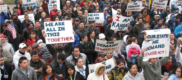 After a protest outside Secretary of State Kris Kobach's office, more than 300 people rallied near the south steps of the Statehouse on Wednesday.