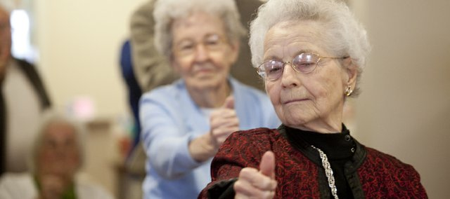 Lawrence resident Thelma Hehn tries to maintain her balance as she keeps an eye on her thumb during a session on strength, balance and precautions against falling at Meadowlark Estates.